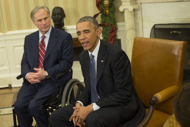 President Barack Obama sits next to Republican Texas Gov. Greg Abbott as he speaks to reporters in the Oval Office of the White House. On Friday, Abbott's office announced the state will not accept Syrian refugees brought to the United States to resettle, claiming the government isn't doing enough to screen them as potential security threats. File Photo by Kevin Dietsch/UPI