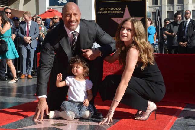 Dwayne Johnson (L), pictured with Lauren Hashian (R) and daughter Jasmine, helped out Hashian as she breastfed Sunday. File Photo by Jim Ruymen/UPI