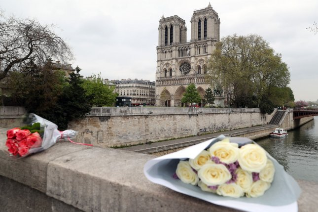 Flowers are laid before Notre Dame Cathedral after a devastating fire in Paris, France, on April 16, 2019. File photo by Eco Clement/UPI