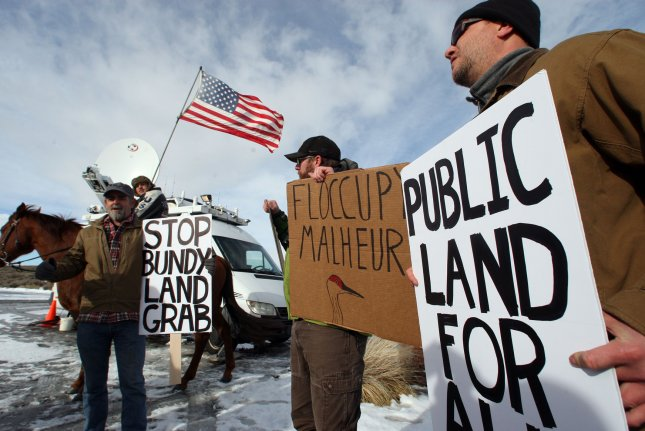 L-R, biologists Kieran Suckling, Cody Martz and Taylor McKinnon hold protest signs at the Malheur National Wildlife Reserve on January 16, 2016, in Burns, Ore. On February 11, 2016, the last four remaining armed occupiers at the refuge surrendered after a 41-day standoff that left one dead. File Photo by Jim Bryant/UPI
