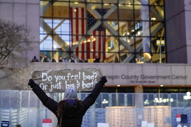 Sheridan Lair of Minneapolis, Minn., holds up a sign as she protests in front of the site of the Derek Chauvin murder trial at the Hennepin County Government Center in Minneapolis on April 19. Photo by Jemal Countess/UPI