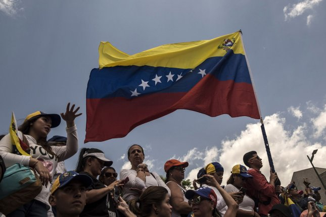 Supporters of Venezuelan opposition leader and self-proclaimed interim president Juan Guaido demonstrate with a Venezuelan national flag in Caracas on March 4, 2019. Photo by Marcelo Perez/UPI