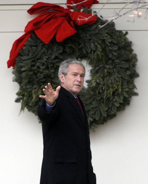 U.S. President George W. Bush passes a wreath on the colonnade in the Rose Garden of the White House in Washington en route to Camp David for Christmas on December 21, 2007. (UPI Photo/Roger L. Wollenberg)