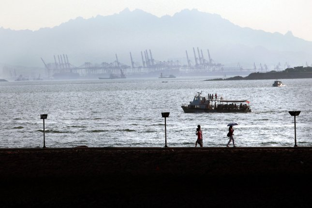 Chinese tourists visit a beach located across a bay from a naval base in the coastal city Qingdao, a major port in eastern Shandong Province, on August 18, 2014. Qingdao is home to China's North Sea Fleet, considered one of the country's most important naval fleets due to its proximity to South Korea, Japan and Taiwan. File photo by Stephen Shaver/UPI