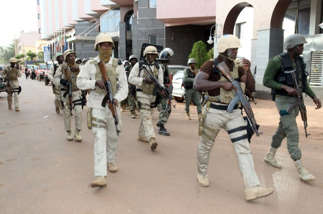 Security forces walk close the Radisson Blu hotel hotel in Bamako, Mali, on Nov. 20, 2015, when al-Qaida gunmen assaulted the facility, killing at least 19 people. Malian authorities on Nov. 22, 2015, said they were seeking at least three suspects in connection with the attack. Two others died when security forces stormed the hotel. Photo by Hapep/ UPI