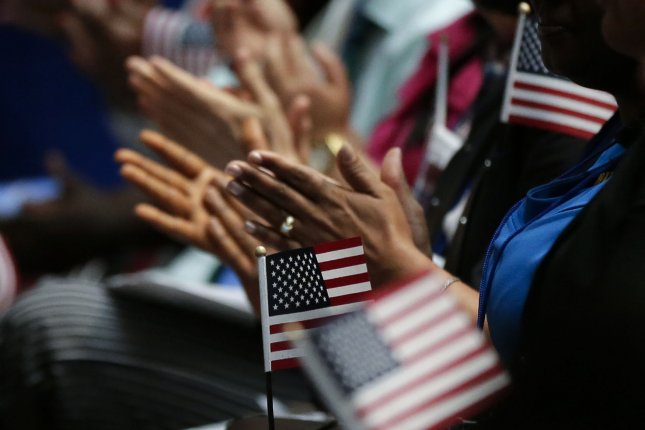 New citizens of the United States applaud during a special naturalization ceremony at the Stephen A. Schwarzmann Building of the New York Public Library in New York City on July 3, 2018. File Photo by John Angelillo/UPI