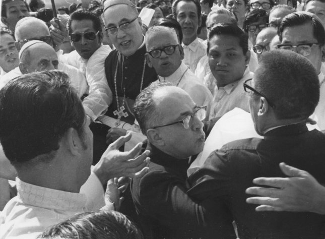 Msgr. Pasquale Macci (C), private secretary to Pope Paul VI, pushes away a crew-cut, cassock-clad man (R) trying to attack the pope with a knife at the airport in Manila, Philippines, shortly after the Pope's arrival on November 27, 1970. UPI File Photo