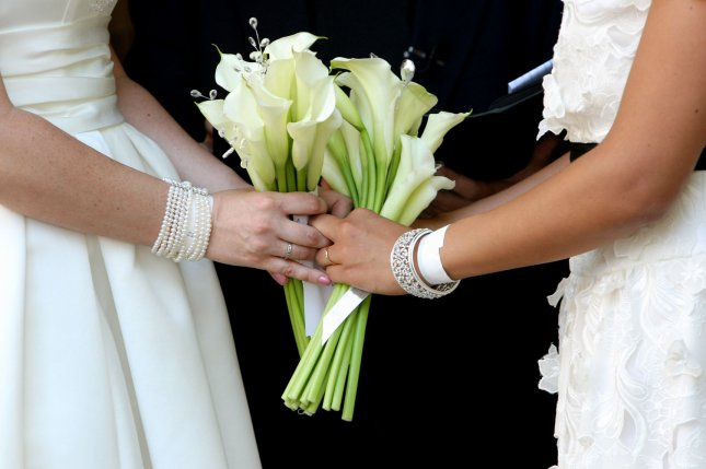 Jen (L) and Rose Nagle-Yndigoyed hold hands as they exchange wedding vows in Central Park in New York City nearly a week after New York State legalized same-sex marriage. A judge has opened the door for same-sex couples in Idaho to wed starting as soon as Friday. (UPI /Monika Graff)
