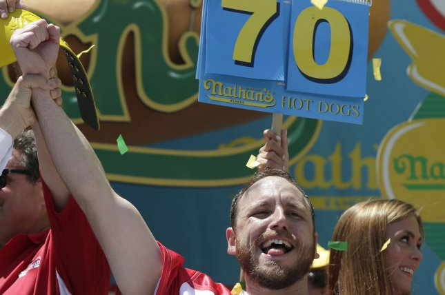 Joey Chestnut celebrates after his victory at the Nathan's Famous Fourth of July International Hot Dog Eating Contest 100th anniversary on July 4, 2016, in Coney Island. Chestnut regains his title eating 70 hot dogs and buns. The Nathan's Famous Fourth of July International Hot Dog Eating Contest has occurred each July 4th in Coney Island since 1916. Photo by John Angelillo/UPI