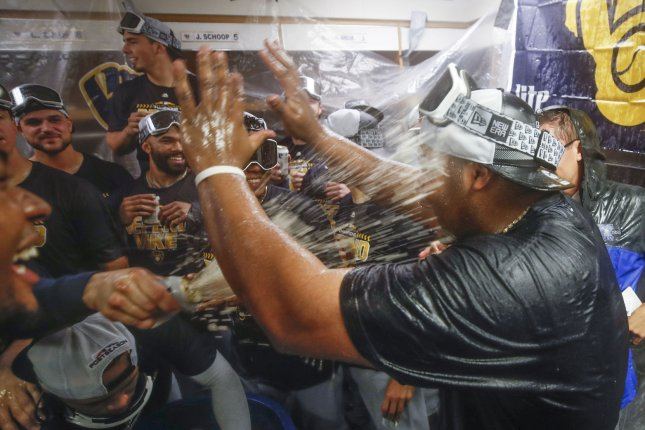 Milwaukee Brewers players celebrate after defeating the Chicago Cubs and winning a National League Central Division title at Wrigley Field on October 1 in Chicago. Photo by Kamil Krzaczynski/UPI