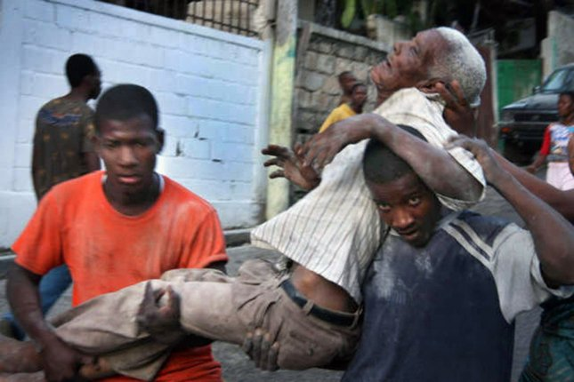 An injured man is carried by survivors of a magnitude-7 earthquake in Port-au-Prince, Haiti on January 13, 2010. Photo by Matthew Marek/American Red Cross/UPI