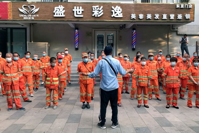 Municipal workers wearing protective face masks prepare for their day shift in Beijing on June 15. A workers' rights organization said Tuesday the coronavirus has dwindled employee hours worldwide. Photo by Stephen Shaver/UPI