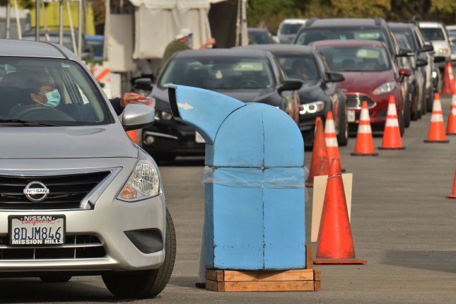 Residents in Los Angeles County, Calif., deposit coronavirus tests in a receptacle bin at a testing site. Health officials have said they will stop providing the test after federal regulators raised questions about its accuracy. Photo by Jim Ruymen/UPI