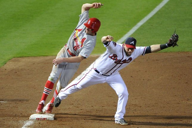 Atlanta Braves third baseman Chris Johnson (R) fields the grounder to force out St. Louis Cardinals' Peter Bourjos (8) during the sixth inning at Turner Field in Atlanta, May 5, 2014. Bourjos was initially called safe but the call was challenged by Atlanta manager Fredi Gonzalez and overturned.UPI/David Tulis
