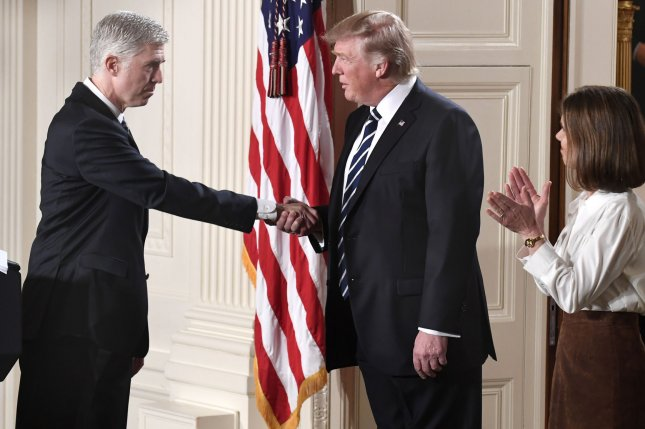 President Donald Trump (C) shakes hands with 10th Circuit Court of Appeals Judge Neil Gorsuch Tuesday in Washington, D.C. Trump nominated Gorsuch for the Supreme Court. Photo by Mike Theiler/UPI
