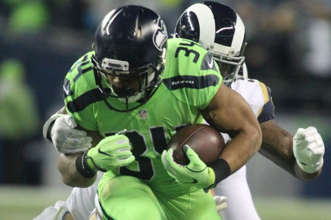 Seattle Seahawks running back Thomas Rawls (34) is wrapped up by Los Angeles Rams Los Angeles Rams middle linebacker Alec Ogletree (52) after gaining 4-yards at CenturyLink Field in Seattle, Washington on December 15, 2016. The Seahawks beat the Rams 24-3. Photo by Jim Bryant/UPI