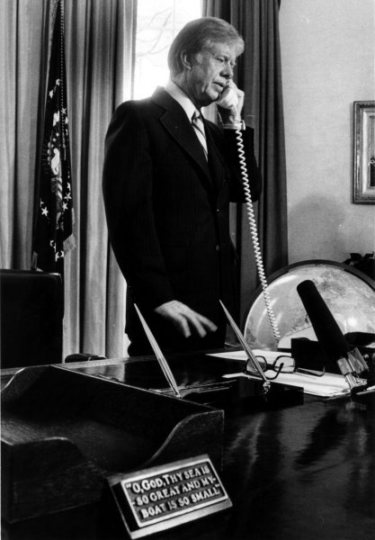 President Jimmy Carter receives a telephone call on March 28, 1980, in the Oval Office. On January 23, 1980, Carter reinstated the Selective Service System. UPI File Photo