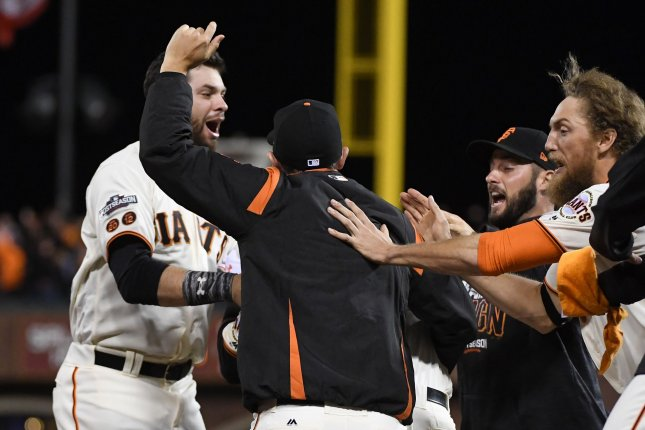 San Francisco Giants' Joe Panik (L) is congratulated after his double scored Brandon Crawford in the thirteenth inning for the 6-5 win over the Chicago Cubs during National League Division Series Game 3 at AT&T Park in San Francisco, October 10, 2016. Photo by Terry Schmitt/UPI