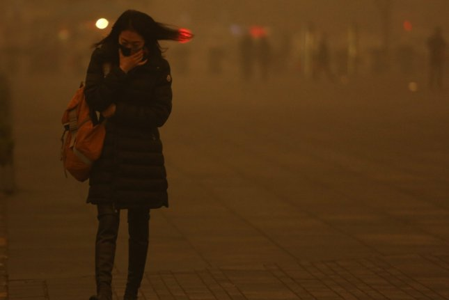 A woman wears a face mask while walking in Beijing, China, amid hazardous levels of air pollution. Wednesday's report said people in Asia, Africa and the Middle East are the most affected by air pollution. File Photo by Stephen Shaver/UPI