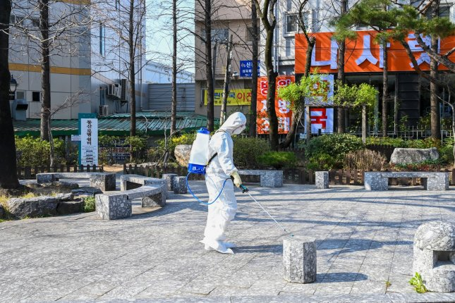 A healthcare worker in a biohazard suit sprays disinfectant outside Keimyung University Dongsan Medical Center, a hospital in Daegu, South Korea, on March 24. File Photo by Thomas Maresca/UPI