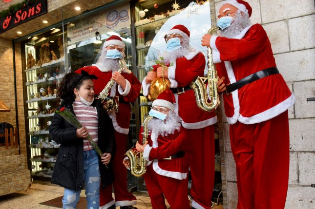 A Palestinian girl looks at a Santa Claus display Tuesday, Christmas Eve, in Bethlehem, West Bank. The COVID-19 pandemic hit the biblical city of Jesus' birth in early March and led to closed borders and no tourists for nine months. Photo by Debbie Hill/UPI