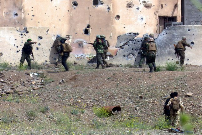 Iraqi soldiers and Shia volunteers are seen as they fight Islamic State (IS) militants, in Tikrit, northern Iraq, on April 1, 2015, a day after the Iraqi Prime Minister Haider al-Abadi declared victory in the weeks-long battle to retake the strategic city from the Islamic State. Reports on April 4 accused Shia militia of looting and Iraqi police of executing captured IS militants, while mobs reportedly burned hundreds of homes in the city. Photo by Alaa Mohamed/UPI