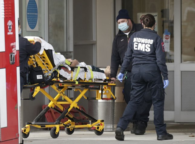 Medial workers push a patient on a stretcher from an ambulance into the Emergency Room entrance of Maimonides Medical Center in New York City on Friday. Photo by John Angelillo/UPI