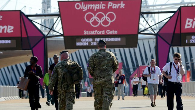 British Army troops walk beneath the Olympic Park sign with the Olympic Stadium in the background on July 24, 2012 in Stratford, East London. The army began to patrol Olympic Park after a private security firm came up short on the number of security personnel needed for the London 2012 Olympic Games. UPI/Pat Benic
