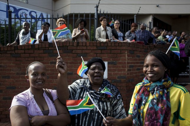 People pay their respects as the body of former South African president Nelson Mandela is transported to the Union Buildings in Pretoria, South Africa, where it will lie in state for the public to view on December 12, 2013. Mandela will be buried on December 15th. UPI/Charlie Shoemaker