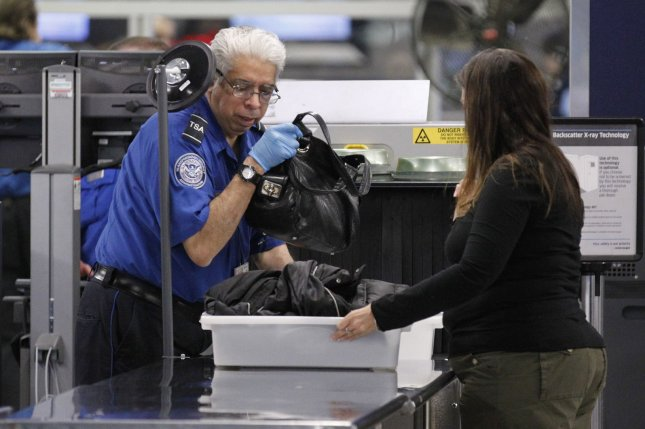 A TSA screener helps a passenger at a security checkpoint at O'Hare International Airport on November 24, 2010, in Chicago. On July 26, TSA announced it will require extra security measures on electronics bigger than a cell phone. File Photo by Brian Kersey/UPI