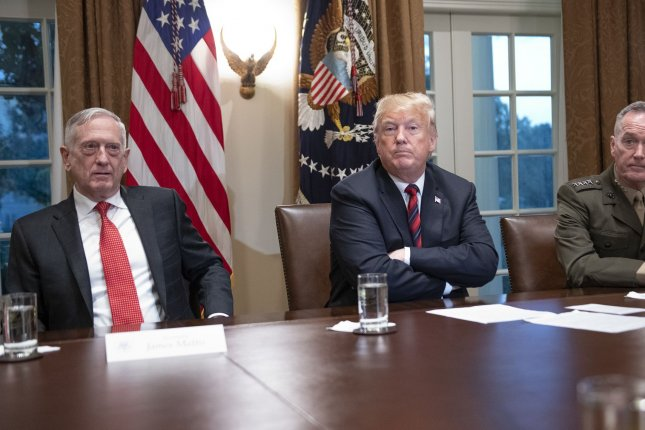 President Donald Trump speaks to reporters in the Cabinet Room of the White House on October 23, as Defense Secretary James Mattis listens at left. Photo by Ron Sachs/UPI