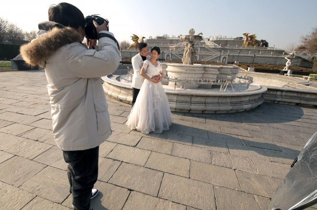 Newlyweds pose for a photo. The U.S. marriage rate has dropped to the lowest numbers on record, the National Center for Health Statistics said Wednesday. File Photo by Stephen Shaver/UPI