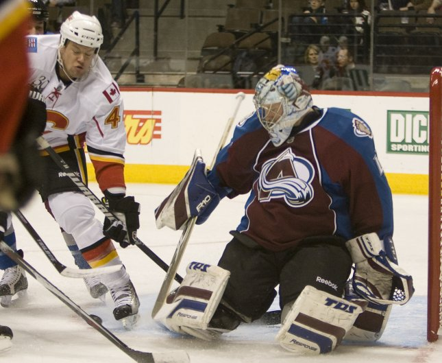 Colorado Avalanche goalie Craig Anderson (R) makes a save against Calgary Flames defenseman Aaron Johnson during the first period at the Pepsi Center in Denver on December 13, 2009. Calgary and Colorado face off in a battle for first place in the Northwest division. UPI/Gary C. Caskey...