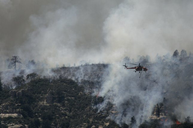 A helicopter battles a fire in Oak Creek Canyon in northern Arizona in 2006. (UPI Photo/Will Powers)