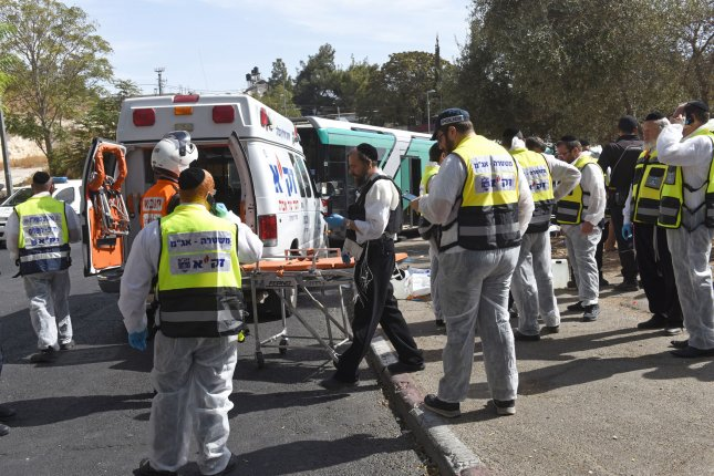 Israeli ZAKA emergency response personnel work at the scene of a shooting and stabbing terror attack on a bus in Jerusalem, Israel, October.13, 2015. Two Palestinian men boarded a bus in Jerusalem and began shooting and stabbing passengers. In a separate Jerusalem attack a Palestinian rammed a car into a bus station before stabbing bystanders. Three Israelis and one attacker were killed and more than thirty wounded. Photo by Debbie Hill/ UPI