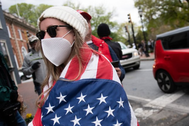 A woman wears an American flag and a face mask in Annapolis, Md., on April 18. Wednesday saw another surge of new cases in the United States, nearly60,000. File Photo by Kevin Dietsch/UPI