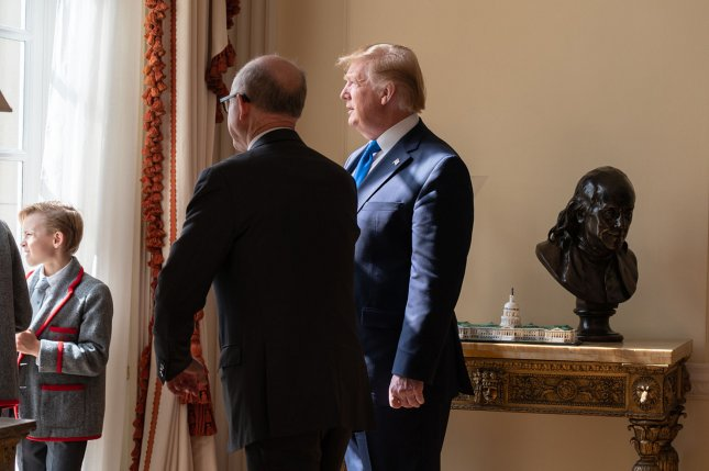 President Donald Trump and U.S. Ambassador to Britain Woody Johnson look out on June 3, 2019, from a window at Winfield House, the official residence of the U.S. ambassador. Both denied allegations that Trump asked Johnson to push to have the British Open at Trump's Scottish resort.  File Photo by Shealah Craighead/White House