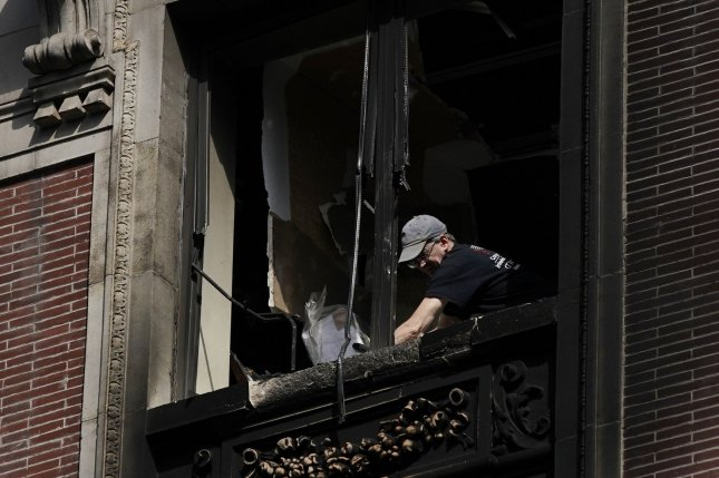 Workers clean debris after six people, including four children, were killed in New York City's deadliest fire since 2017 in Harlem on Wednesday. Photo by John Angelillo/UPI