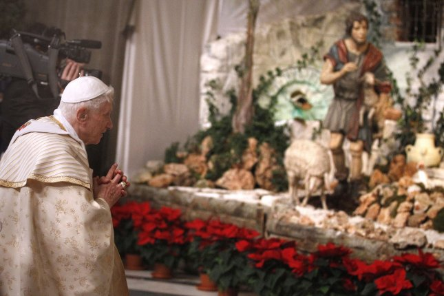 Pope Benedict XVI prays at the nativity scene after celebrating Christmas Eve Mass in St. Peter's Basilica at the Vatican on December 24, 2012. On December 25, 2007, the pope revealed a new-style nativity scene in the Vatican's St. Peter's Square. It depicted Jesus' birth in Joseph's house, with no mention of a manger or journey to Bethlehem. File Photo by Stefano Spazani/UPI