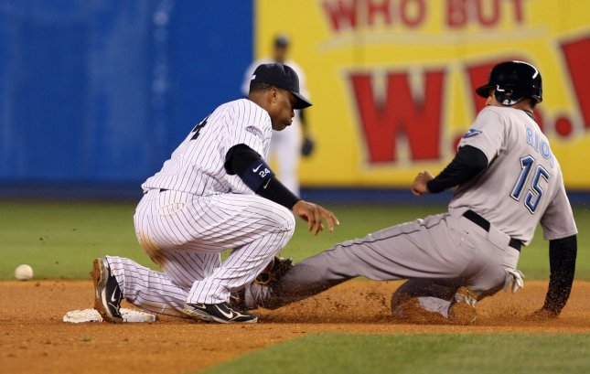 Toronto Blue Jays Alex Rios (15) slides into second base safely as the ball gets by New York Yankees Robinson Cano in the fourth inning at Yankee Stadium in New York City on April 3, 2008. (UPI Photo/John Angelillo) .