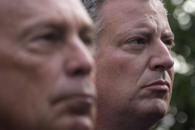 New York Mayora Bill de Blasio (R) stands near former New York Mayor Michael Bloomberg. UPI/Adrees Latif/POOL