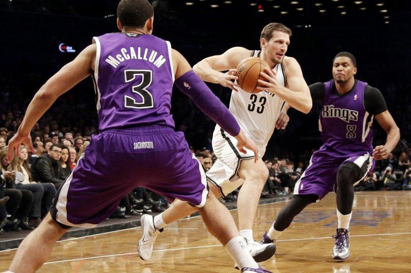 Brooklyn Nets' Mirza Teletovic drives the basketball between former Sacramento Kings' Ray McCallum and Rudy Gay. UPI/John Angelillo