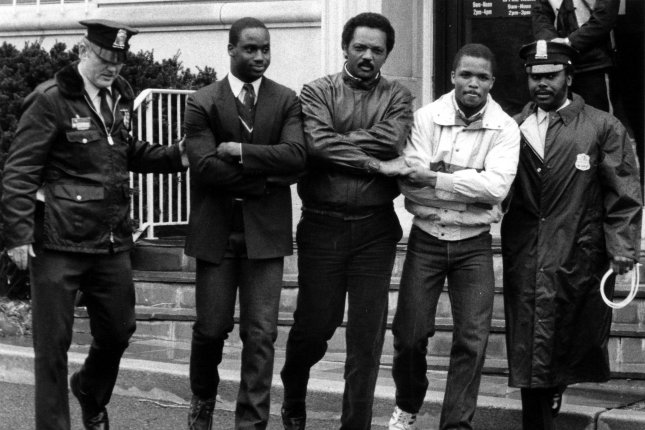 Civil rights leader Jesse Jackson (C) is flanked by his sons, Jonathon and Jesse Jr., as they sing We Shall Overcome while being arrested on March 11, 1985, on the front steps of the South African embassy in Washington, D.C. They were demonstrating against the country's policy of racial segregation. Photo by Ron Bennett/UPI