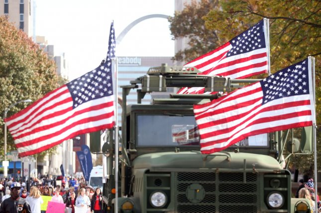 An Army vehicle decorated with American flags makes its way through the Veterans Day parade in St. Louis on Saturday. Photo by Bill Greenblatt/UPI