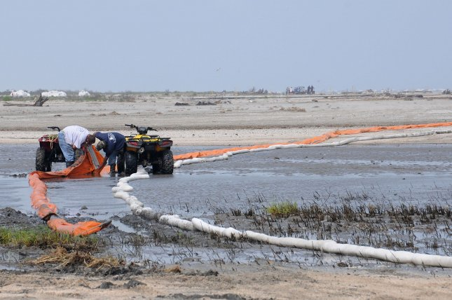 HS&E workers place oil containment boom on low areas of a beach in Fourchon, Louisiana May 14, 2010. The boom is place in the low areas to prevent oil from getting into the nearby marsh when water from the ocean flows into it when sea levels are at their highest levels. UPI/Patrick Kelley/US Coast Guard