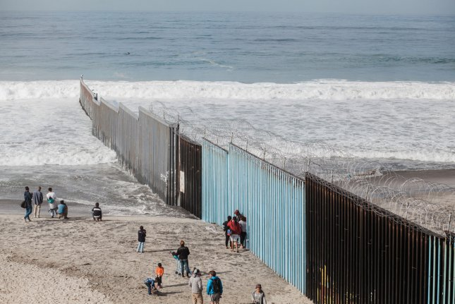 People stand on the beach on the Mexican side of the border fence, at left, in Tijuana, Mexico, on November 28. File Photo by Ariana Drehsler/UPI