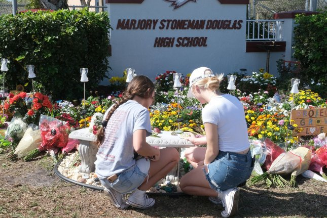 Students lay down notes and flowers at a makeshift memorial in front of Marjory Stoneman Douglas High School in Parkland, Fla. on Thursday. Photo by Gary Rothstein/UPI
