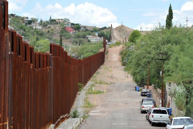 The border fence between the United States and Mexico stretches to the west near Nogales, Arizona on July 13, 2014. More than 57,000 children from Central America have crossed the U.S. border alone since October 1, 2013. President Obama has asked congress for $3.7 million to deal with the influx. UPI/Art Foxall