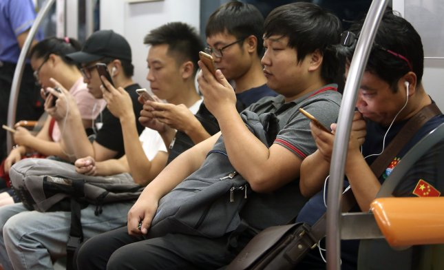 Chinese students use their smartphones while commuting to school on a subway in Beijing on September 13, 2017. File Photo by Stephen Shaver/UPI