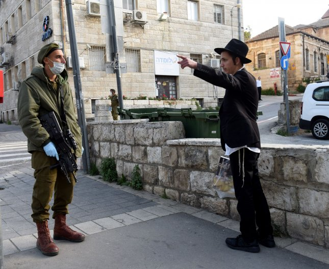 An Israeli soldier wears a mask and gloves, as protection from the coronavirus, while enforcing movement restrictions in Jerusalem on Tuesday ahead of Passover. Photo by Debbie Hill/UPI